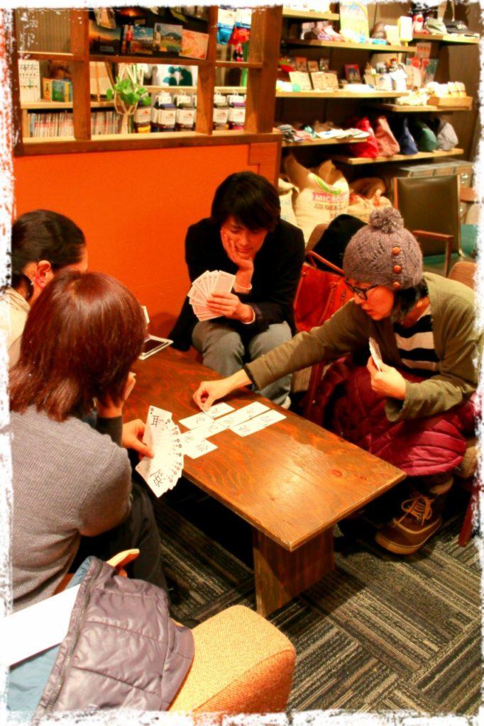 北海道、倶知安駅前にあるカフェSproutで、閉店後、カード遊びする大人4人