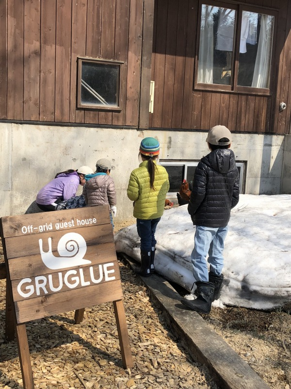 Off-grid guest house GRUGLUE(オフグリッドゲストハウスグルグル)でにわとりに遊んでもらう子供たち。